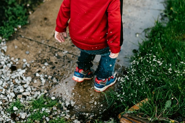 Boy jumps in puddle-min