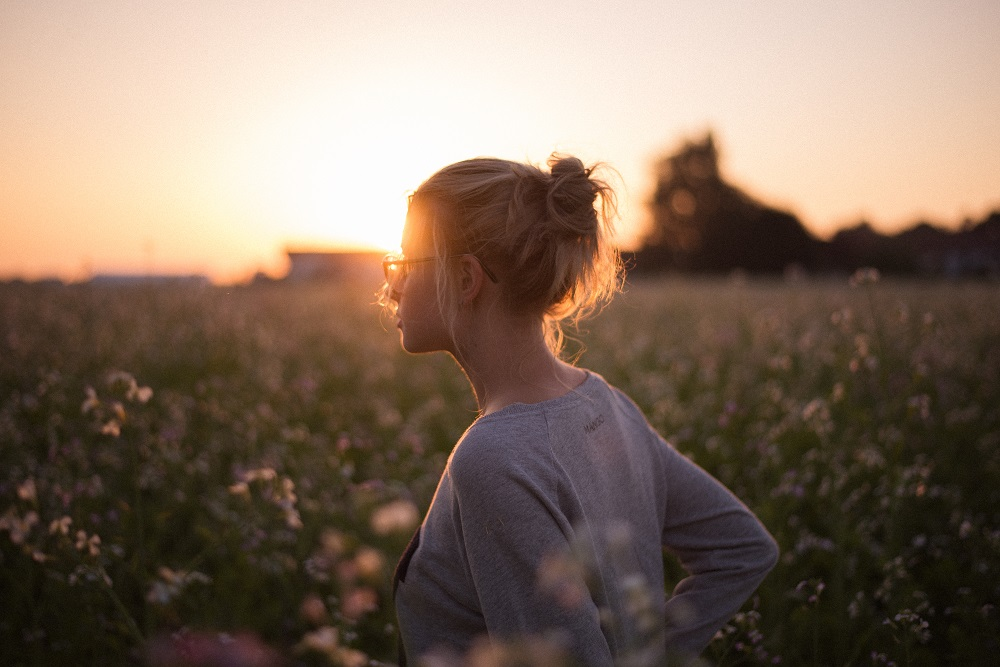 Woman in field at sunset