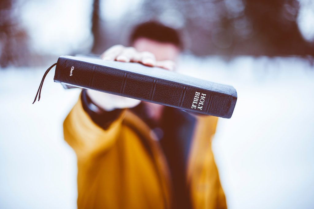Close up shot of a Holy Bible spine, held up by a man wearing a yellow jacket blurred in the background